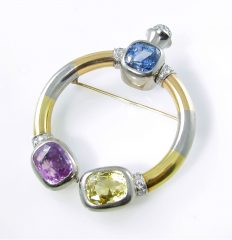 A platinum, yellow and rose gold, diamond, and colored sapphire brooch circa 1940.