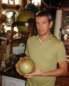 Jeffrey Denke posing with globe